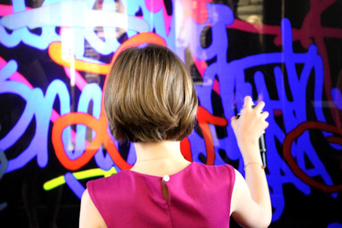 Une femme faisant des graffitis sur le mur interactif