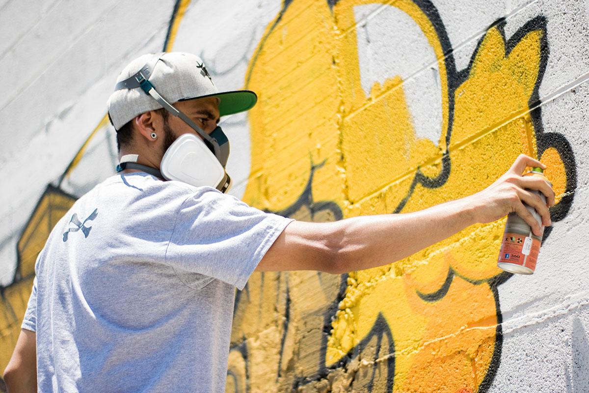 Une personne faisant un graffiti sur un mur blanc