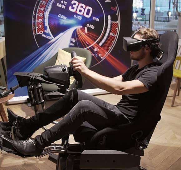 joueur équipé d'un casque VR installé au volant d'un siège de simulateur de conduite auto