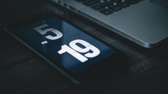 téléphone avec timer posé sur un bureau à côté d'un ordinateur